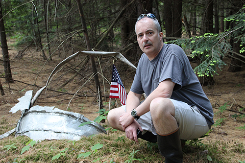 With the help of Pat Cutter and the permission of Roy Sell, Peter Ferraro planted an American flag at the site of the crash of an Air Force plane that crashed in Andover in 1959, killing all aboard. Peter is shown here at the crash site with the flag and some of the wreckage. Photo: Marc Goldstein