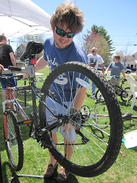 "Geordie Sousa '13, of Colby-Sawyer College and the Kearsarge Valley Transition Initiative, was one of the volunteer ""mechanics"" at the Community Bike Tune-Up and Swap in New London on May 4. Together with Professor Harvey Pine of Andover and fellow student Doug Foley '15, they estimate they tuned up 35 bikes."