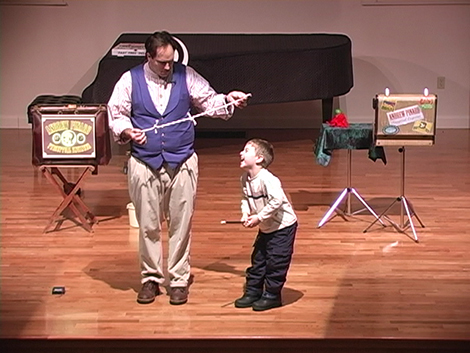 A volunteer assistant from the audience assists Andrew Pinard during a performance of Alejandro's Olde Tyme Magik Showe. At the annual meeting of the Friends of the Wilmot Public Library, Pinard will be on stage at 7 PM on Thursday, May 16, at the Wilmot Town Hall, North Wilmot Road, just off Route 4A in Wilmot Center. More information is available at 526-6804.