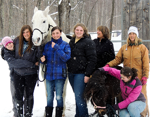 Alicia Barry, Katie Nelson, Taylor Drewniak, Leah Brodie, Terry Stoecker, Allison Barry, and Jacqui Morris (kneeling) pause on a snowy day for a photo with two of their horses. The big white one is Clint, a rescue horse. Photo: Chuck Will